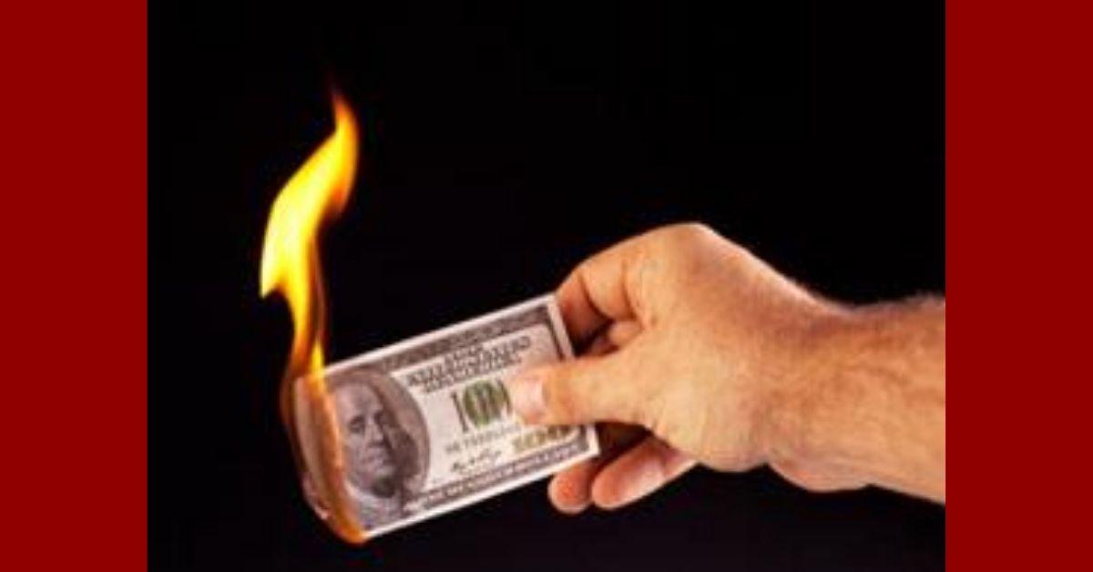 burning dollar in hand